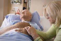 Пожилой мужчина и его дочь. Женщина сидит человек в больничной койке — стоковое фото