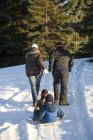 Rear View Of Happy Caucasian Family, Parents Carrying Sled With Kids On Winter Snow — Stock Photo