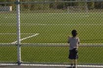 Мальчик смотрит на футбольное поле через цепной забор — стоковое фото