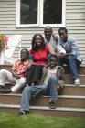 Портрет счастливой афро-американской семьи, сидя на лестнице их дома и, глядя на камеру — стоковое фото