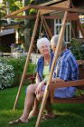 Senior couple sitting on swing and looking at each other — Stock Photo