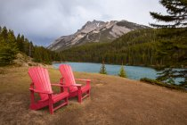 Two Red Adirondack Chairs On A Grassy Hill In Alberta's Mountains And Lakes; Alberta, Canada — Stock Photo