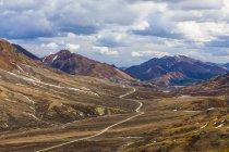 Vista della Valle di montagna con acqua di ruscello di fiume e picchi sotto il cielo nuvoloso — Foto stock