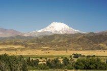 Schneebedeckte Vulkan überragt den Ausläufern der Anden und Ackerland; Mendoza, Argentinien — Stockfoto