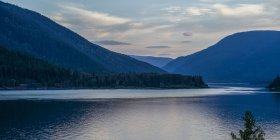 Clear calm lake water with trees on shore with hills — Stock Photo
