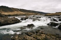 Water Flowing Over Rocks On A Landscape Under A Cloudy Sky; Iceland — Stock Photo