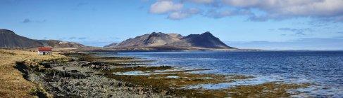 Краєвид вздовж узбережжя з гірських вершин на відстані і невеликий будинок з червоний дах уздовж на елегантній, Snaefellsnes півострова; Ісландія — стокове фото