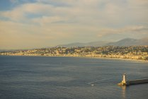 A Lighthouse At The End Of The Pier And Along The Coastline Of The French Riviera; Nice, Cote D'azur, France — Stock Photo