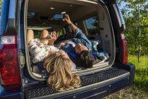 Jeune couple portant sur la voiture et regarder dans smartphone pendant la journée — Photo de stock