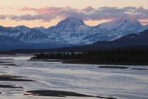 Гірська річка зі снігом покриті піків на тлі — стокове фото