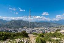 A Cruz e a vista do topo de uma montanha com vista para Mostar e mostrando a separação entre a cidade; Mostar, Bósnia e Herzegovina — Fotografia de Stock
