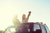 Casal jovem parado no carro com a parte superior da aleta e fazendo selfie contra a luz do sol — Fotografia de Stock