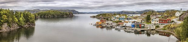 Panoramic view of sea water, mountains and small village on shore  and trees on another shore — Stock Photo