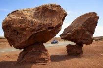 Formazione geologica conosciuta come 'bilanciamento delle rocce' situata vicino al traghetto di Lee, Az sulla terra nativa americana, come visto in piena estate con un'auto che viaggia sulla Highway e Blue Sky Beyond; Arizona, Stati Uniti d'America — Foto stock