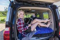 Glückliches blondes Mädchen liegt mit digitalem Tablet in der Hand am Auto und blickt in die Kamera — Stockfoto