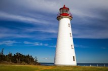 Lighthouse standing on shore against water during daytime — Stock Photo