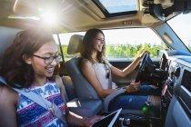 Две девушки сидят в машине, в то время как одна за рулем другой смотрит на цифровой планшет — стоковое фото