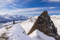 Одинокий мужчина, стоя на краю горной вершины покрыты снегом — стоковое фото