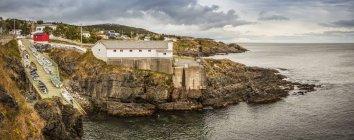 Fishing sheds and cliffs with stratum along the Atlantic coastline; Bonavista, Newfoundland, Canada — Stock Photo