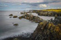 Litorale roccioso con massi sopra acqua di mare sotto cielo nuvoloso — Foto stock