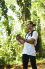 A young man stands on a trail wearing a backpack and taking a picture with a camera while on a hike; Hawaii, United States of America — Stock Photo