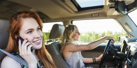 Two girls sitting in car while one driving another one speaking on cell phone — Stock Photo
