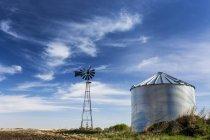 Старая мельница с большим металлическим зерном с интересными облаками и голубым небом; Beiseker, Альберта, Канада — стоковое фото