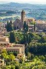 Edificios de piedra e iglesia en el paisaje cubierto de árboles y colinas en el fondo; Siena, Toscana, Italia - foto de stock