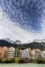 Colourful buildings along river bank with snow-covered mountain peaks, dramatic clouds and blue sky overhead; Innsbruck, Tyrol, Austria — Stock Photo