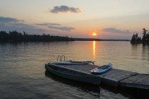 Сонця над над спокійне озеро з док, каное і весло плати на передньому плані; Лісове озеро, Онтаріо, Канада — стокове фото