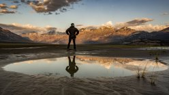 Man standing with reflection in a pool of water looking out over the Saint Elias Mountains at sunset, Kluane National Park and Reserve, Destruction Bay, Yukon, Canada — Stock Photo