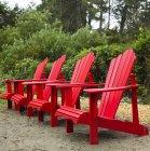 Four red Adirondack chairs in a row on Chesterman Beach, Vancouver Island, Pacific Rim; Tofino, British Columbia, Canada — Stock Photo