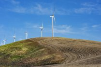 Wind farm wind turbines on a farmer's ploughed field combining green energy with agriculture, Eastern Washington; Dayton, Washington, United States of America — Stock Photo