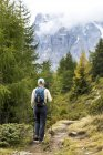 Female hiker along alpine trail with cloud covered mountains in the background, Sesto, Bolzano, Italy — Stock Photo