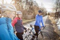 Три молодые женщины, на их велосипеды на след на рассвете; Анкоридж, Аляска, Соединенные Штаты Америки — стоковое фото