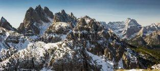 Rugged snow-covered mountain range with blue sky; San Candido, Bolzano, Italy — Stock Photo
