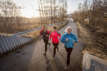 Three young women running on a trail at sunrise; Anchorage, Alaska, United States of America — Stock Photo