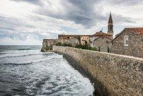 Каменная стена вдоль береговой линии со зданиями и церковной башней; Будва, Опстина Будва, Черногория — стоковое фото