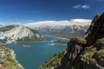 Vista desde la cima de la cordillera mirando hacia abajo en el lago alpino colores y gama de la montaña en la distancia con el cielo azul y nubes; País de Kananaskis, Alberta, Canadá - foto de stock