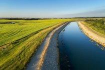 Un canal de riego con un camino que corre a su lado y el cielo azul, al este de Calgary; Alberta, Canadá - foto de stock