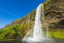 Cascata di Skogafoss con cielo blu e arcobaleno nella nebbia; Islanda — Foto stock