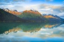 Чёрная гора и Спящая сестра в горах Кенай размышляют о озере Кенай на восходе солнца, альпенглоу на вершинах. Чугачский национальный лес, южная и центральная Аляска; Аляска, Соединенные Штаты Америки — стоковое фото