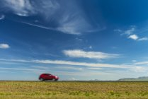Red car driving on open road near Hella with Hekla volcano in the distance; Iceland — Stock Photo