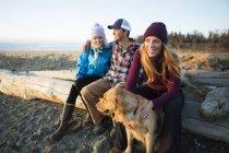Ein junges paar und ein Freund mit einem Hund sitzen auf ein Stück Treibholz an einem Strand, Blick auf das Meer bei Sonnenuntergang; Anchorage, Alaska, Vereinigte Staaten von Amerika — Stockfoto