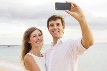 Feliz jovem caucasiano casal tomando selfie contra bela praia — Fotografia de Stock