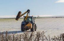 Coupe-haies tracteur sur le point de tailler en hiver une haie boudaire au bord du champ Flodden, Northumberland Nord ; Northumberland, Angleterre — Photo de stock
