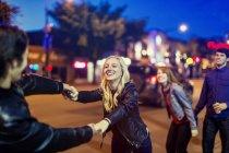 Две молодые пары играют на тротуаре рядом с городской улицей в сумерках — стоковое фото