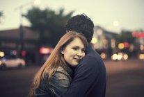 Jeune couple debout et embrassant sur un trottoir — Photo de stock