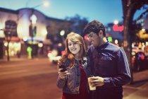 Jovem casal a descer uma calçada na rua ao entardecer enquanto olha para um smartphone — Fotografia de Stock