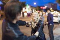 Пара, будучи грайливий на тротуарі місто у нічний час — стокове фото